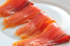 Slices of salmon on a white plate. Close up Royalty Free Stock Images