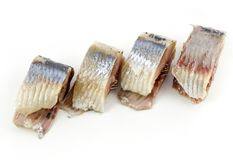 Slices of salted herring on the plate on white background.  Royalty Free Stock Photo