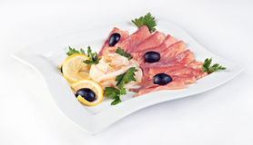 Slices of salted salmon and smoked fat. Served with lemon and olives Stock Image
