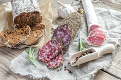 Slices of saucisson and spanish salami on the sackcloth Royalty Free Stock Photo