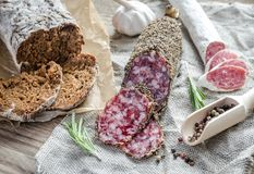 Slices of saucisson and spanish salami on the sackcloth Stock Photos