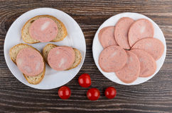 Slices of sausages in plate, sandwiches and tomato cherry Stock Images