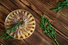 Slices of Scandinavian herring fillet with spices and dill in a transparent jar royalty free stock image