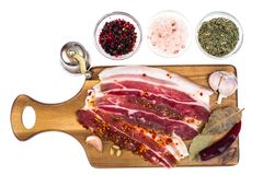Slices of smoked bacon with light on wooden kitchen cutting board. Studio Photo Stock Image