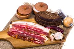 Slices of smoked bacon with light on wooden kitchen cutting board. Studio Photo Royalty Free Stock Photography