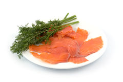 Slices of smoked fish with fennel on a plate. Isolated on white background Stock Photos