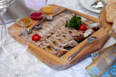 Slices of smoked ham and sausages on a wooden board. Stock Photography