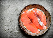 Slices of smoked salmon in the old pan. Stock Image