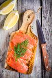 Slices of smoked salmon on a wooden chopping board with dill Royalty Free Stock Photos