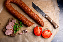 Slices of smoked sausage with spice, herbs and vegetables on the Royalty Free Stock Images