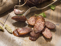 Slices of smoked sausages with bacon, bread, tomatos, herbs, garlic on wooden board Royalty Free Stock Photos