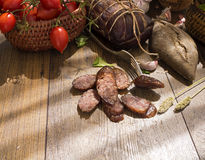 Slices of smoked sausages with bacon, bread, tomatos, herbs, garlic on wooden board Stock Photography