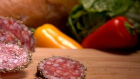 Slices of smoked sausage falls on a wooden board stock video footage