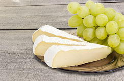 Slices of a soft cheese and white table grapes closeup Stock Image