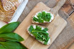 Slices of sourdough bread with butter and wild garlic. Top view Stock Photos