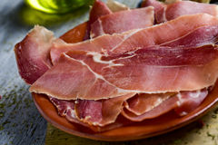 Slices of spanish serrano ham. Closeup of an earthenware plate with some slices of spanish serrano ham, on a gray rustic wooden table, and a cruet with olive oil Stock Photography