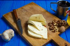 Slices of spicy cheese, served with walnuts,garlic and mug of ho. Memade wine. Tasty homemade food, countryside dinner Royalty Free Stock Images