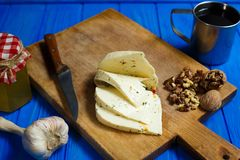 Slices of spicy cheese, served with walnuts,garlic and mug of ho. Memade wine. Tasty homemade food, spicy appetizer, countryside dinner Royalty Free Stock Photos
