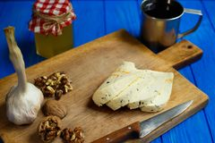 Slices of spicy cheese, served with walnuts,garlic and mug of ho. Memade wine. Tasty homemade food, spicy appetizer, countryside dinner Royalty Free Stock Image