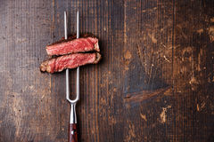 Slices of Steak Ribeye on meat fork. Slices of Medium rare grilled Steak Ribeye on meat fork on dark wooden background Royalty Free Stock Photos