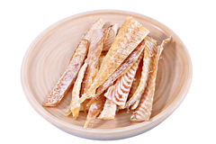 Slices of stockfish on plate made of wood, insulation image. Stock Image