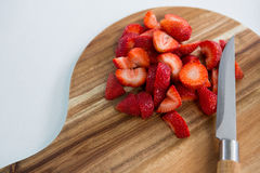 Slices of strawberries on chopping board Stock Images
