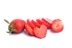 Slices of strawberries with a single strawberry. Slices of strawberries along with a single full strawberry placed over white background Royalty Free Stock Image