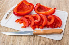 Slices of sweet pepper and kitchen knife Stock Photos