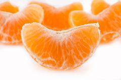 Slices of a tangerine. Slices of a ripe tangerine are fancifully placed on a white background Royalty Free Stock Images