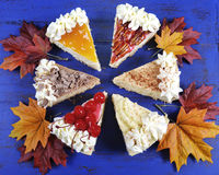 Slices of Thanksgiving Pie on dark blue wood with autumn leaves. Royalty Free Stock Photo