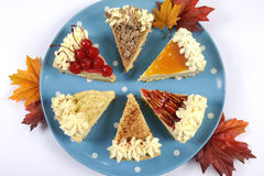 Slices of Thanksgiving Pie on polka dot blue plate with autumn leaves Royalty Free Stock Photos