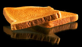 Slices of toasted bread. Two slices of toasted bread reflecting on black background Stock Photography
