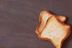 Slices of toasted bread. Background with slices of toast bread and old wooden table Stock Photos