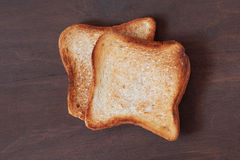 Slices of toasted bread. Background with slices of toast bread and old wooden table Stock Photo