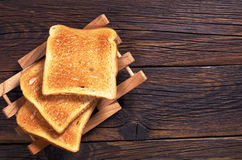 Slices of toasted bread. On dark wooden table, top view. Space for text stock photo