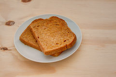 Slices of toasted wheat bread on a wooden table Stock Photo