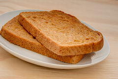 Slices of toasted wheat bread on a wooden table Royalty Free Stock Photos