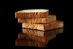 Slices of toasts. Close up of golden slices of toasts on black background with reflection Royalty Free Stock Images