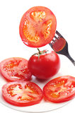 Slices tomato on a fork and in a plate Royalty Free Stock Image