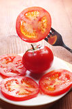 Slices tomato on a fork and in a plate Stock Photo