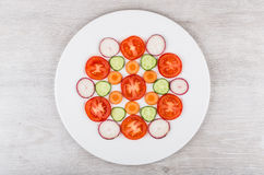 Slices of tomatoes, radishes, carrots and cucumbers in white pla. Slices of tomatoes, radishes, carrots and cucumbers in white glass plate on wooden table. Top Stock Photos