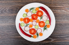 Slices of tomatoes, radishes, cucumbers and dill, peppers in pla. Te on black table. Top view Stock Photo