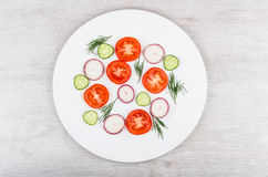 Slices of tomatoes, radishes, cucumbers and dill on white glass. Plate. Top view Royalty Free Stock Photos