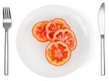 Slices of tomatoes on white plate isolated. Slices of tomatoes on white plate with knife and fork isolated on white background. Healthy food Stock Photo