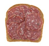 Slices of uncured soppressata dry salami on bread. Top view of a single slice of wheat bread covered with uncured soppressata dry salami isolated on a white Royalty Free Stock Images