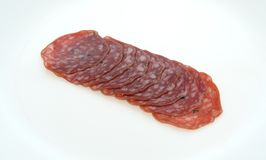 Slices of uncured soppressata dry salami in a row. Several slices of uncured soppressata dry salami in a row on a white plate Royalty Free Stock Images