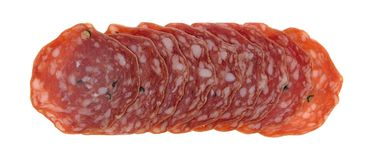 Slices of uncured soppressata dry salami in a row. Top view of several slices of uncured soppressata dry salami in a row isolated on a white background royalty free stock photo