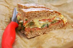 Slices of vegetable bread. Slices of sandwich vegetable bread with cheese, squash, aubergine, tomato, onion and sweet pepper on a stencil paper with a red knife Royalty Free Stock Photo