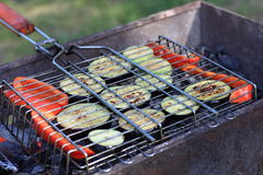 Slices of vegetable marrow and pepper on barbecue grill Stock Photos