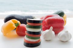 Slices of vegetables, tomatoes, eggplant, garlic, zucchini, bell. Peppers, onions on a background of the sea Stock Image
